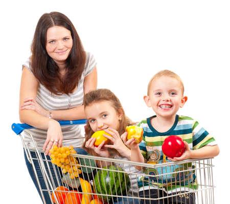 ni�os de compras: Madre lleva a sus hijos en un carrito de la compra aislados en blanco