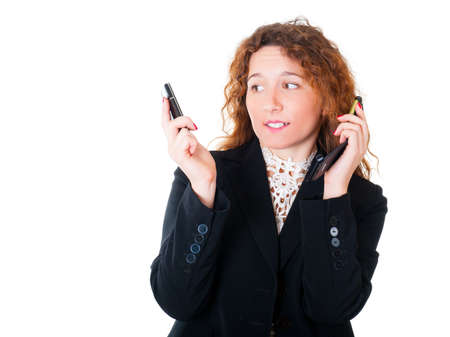 Young business woman with two mobile phones in talks. Isolated over white background. photo
