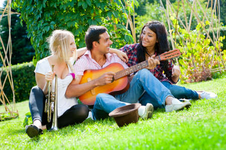 boy playing guitar: Young friends play the guitar and trumpet in the park