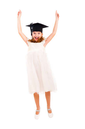 Happy girl dressed Bachelor cap jumping isolated over white photo
