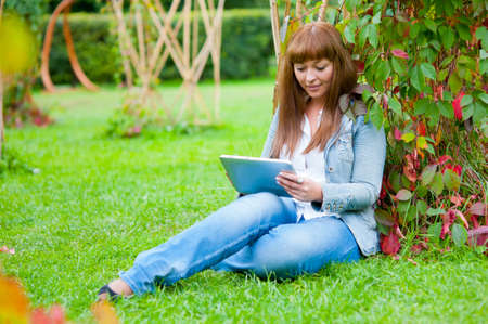 Young woman reading in tablet pc in the park photo