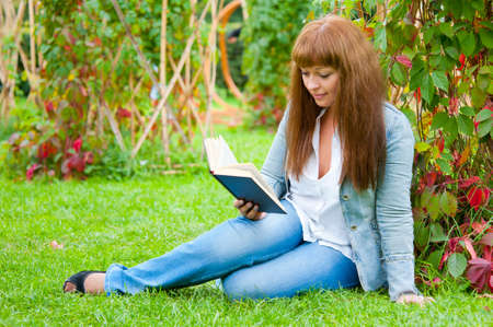 Young woman reading a book sitting on the grass in a park photo