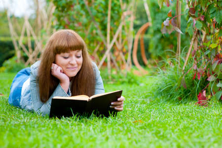 Young woman reading a book lying on the grass in the park photo