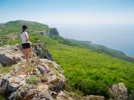 Hiker watch the terrain from the peak of a cliff Stock Photo - 13631631