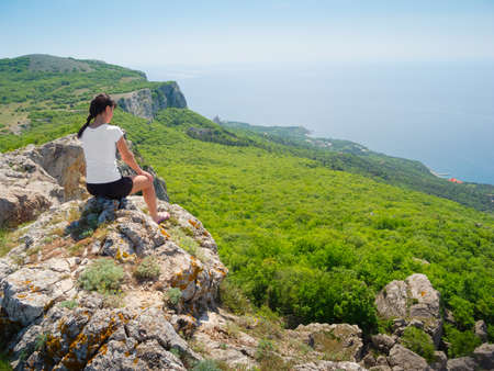 Hiker watch the terrain from the peak of a cliff Stock Photo - 13631636