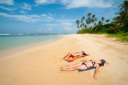 Two women sunbathing on a tropical beach photo