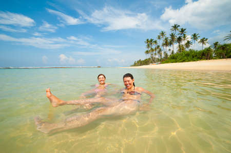 Two women having fun in the ocean on a tropical coast photo