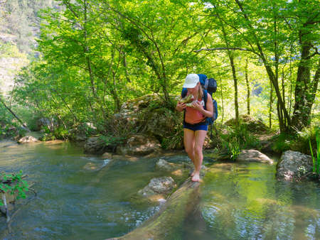 Hiker crosses a river at the ford Stock Photo