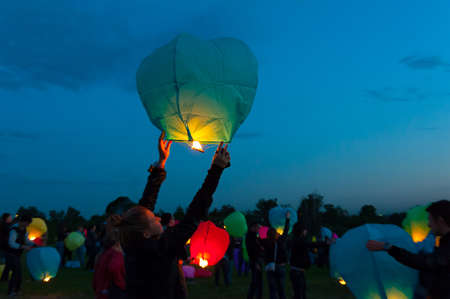 MOSCOW - JUNE 1: Girl releases a floating lantern during the First Day of Summer Festival, on June 1, 2012 in Moscow. During the festival flew more than 1,000 lights. Stock Photo - 14140262