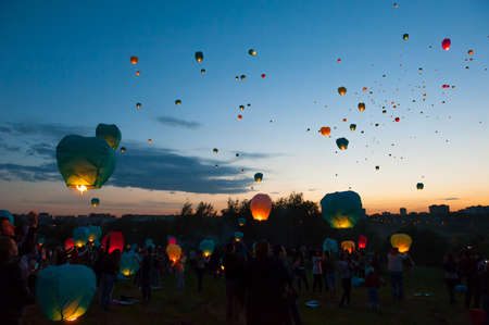 MOSCOW - JUNE 1: Young people release floating lanterns during the First Day of Summer Festival, on June 1, 2012 in Moscow. During the festival flew more than 1,000 lamps. Stock Photo - 14140270