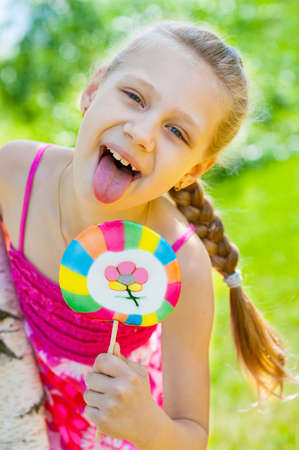 Girl with lollipop shows tongue outdoors