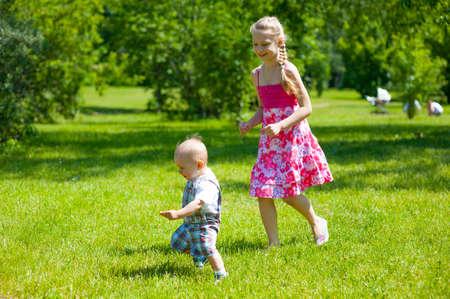 niños jugando en el parque: Los niños que juegan en el césped en el parque Foto de archivo