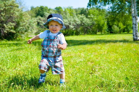 Toddler taking first steps in a park photo