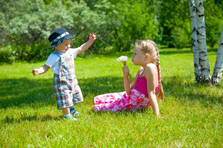Children playing on the lawn in the park photo