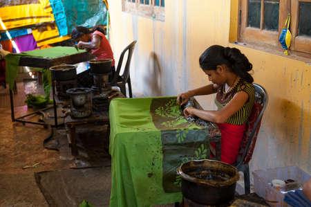 KANDY, SRI LANKA - MARCH 31: Two women, traditional batik painter working in the batik factory on March 31, 2012 in Kandy, Sri Lanka. Batik is a traditional Sri Lankan crafts. Редакционное
