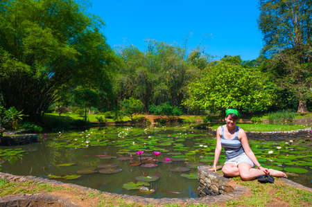 Woman sitting in Botanical Garden landscape in Peradeniya, Kandy, Sri-Lanka photo