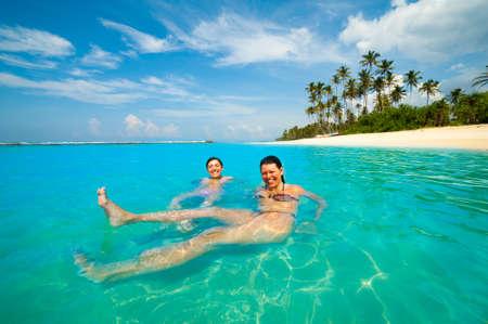 Due donne che hanno divertimento in mare su una costa tropicale