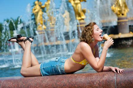 Nice girl enjoys the ice cream. Fountain in background. photo