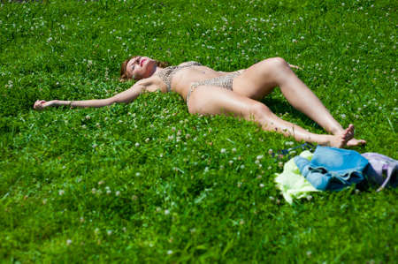 The young girl in a bathing suit sunbathes in park photo