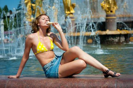 beauty fountain: Nice girl enjoys the ice cream. Fountain in background.