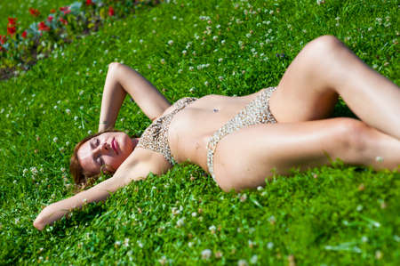 enjoyment: The young girl in a bathing suit sunbathes in park Stock Photo