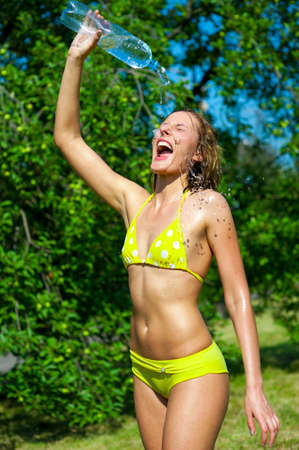 Young woman splashing herself with water outdoors photo