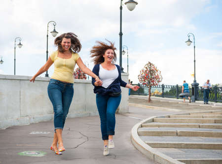Two happy young beautiful women running on the street photo