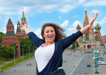 Happy young woman tourist visiting Moscow, Russia. Saint Basils Cathedral and Red Square on the background. photo