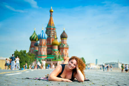 Happy young woman lying on Red Square in Moscow, Russia. Saint Basils Cathedral on the background. photo