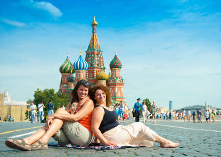 Happy young women visit Red Square in Moscow, Russia. Saint Basil's Cathedral on the background. photo