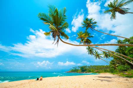 blue lagoon: Spiaggia tropicale in Sri Lanka. Giovane donna seduta sulla sabbia.