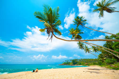 Tropical beach in Sri Lanka. Young woman sitting on the sand. Stock Photo
