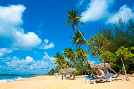 Tropical beach in Sri Lanka. Man reading book sitting on the desk chair. photo