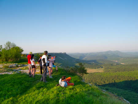 Hikers watch the terrain from the peak of a cliff photo
