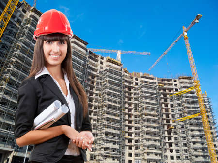 Multi level building construction site. Young business woman at foreground photo