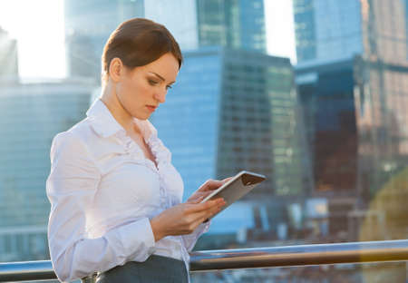 Business woman using tablet PC. Sun beams, lens flare