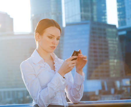 Business woman using smartphone. Sun beams, lens flare Banque d'images