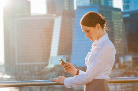 Business woman using smartphone. Sun beams, lens flare Stock Photo