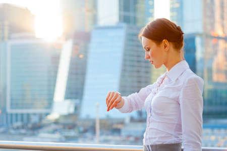 woman clock: Mujer de negocios. �Qu� hora es? . Rayos de sol. Foto de archivo
