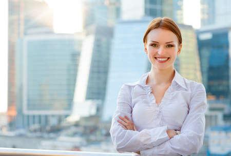 현대 도시 시내 배경에 젊은 비즈니스 여자 웃