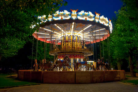 Merry-go-round carousel in the amusement park at evening