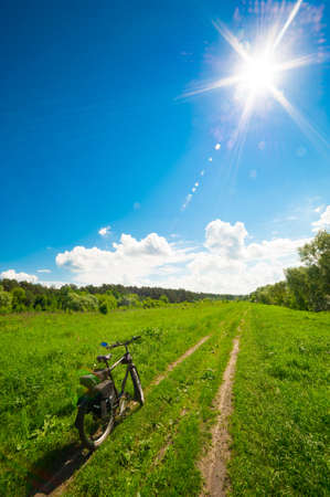 bl: Road bicycle on the rural road in the green meadow, bl
