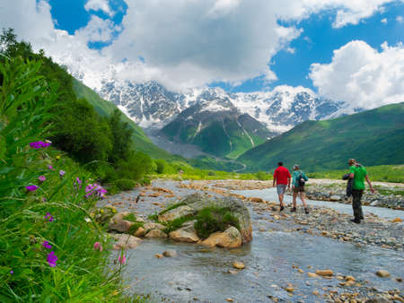 Young hikers trekking in Svaneti, Georgia. Shkhara mountain in the background photo