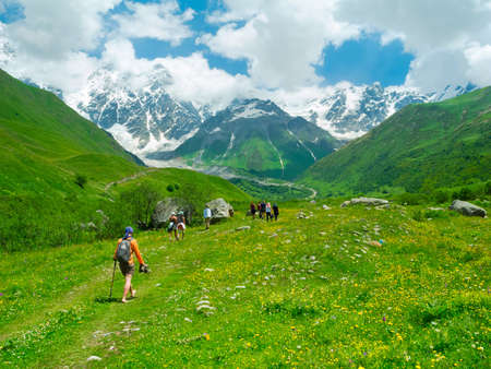 shkhara: Young hikers trekking in Svaneti, Georgia. Shkhara mountain in the background Stock Photo