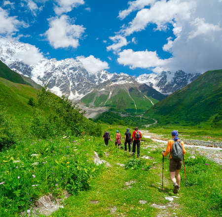 Young hikers trekking in Svaneti, Georgia. Shkhara mountain in the background Standard-Bild