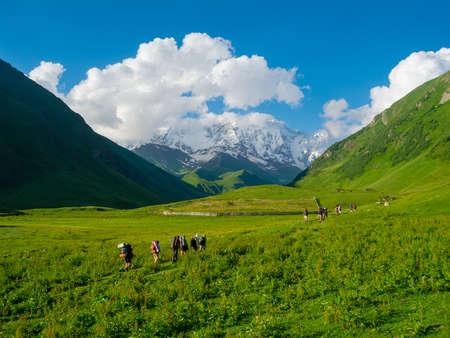 svaneti: Young hikers trekking in Svaneti, Georgia. Shkhara mountain in the background Stock Photo