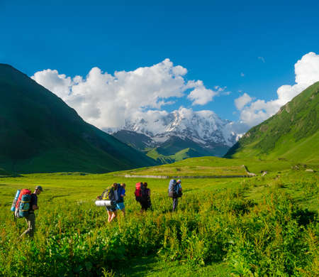 shkhara: Young hikers trekking in Svaneti, Georgia  Shkhara mountain in the background