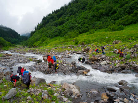Hikers group cross the mountain river ford photo