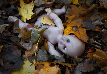unwanted: Abandoned doll lies in the autumn leaves