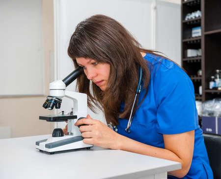 젊은 여자 수의사 의사가 현미경으로 검사를 검사합니다.